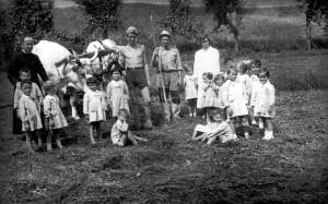 """Battedizzo 1955 - Don Tonino con i bambini della scuola materna di Battedizzo in visita al podere """"Casella""""."""