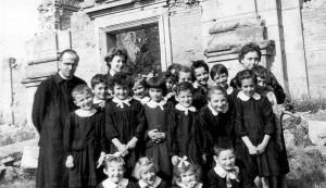 Badolo 1950 - Don Tonino con un gruppo di ragazzi davanti ai ruderi della chiesa completamente distrutta durante la seconda guerra mondiale.