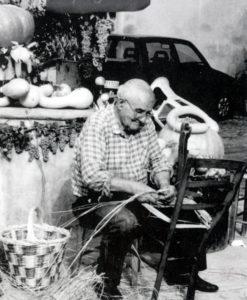 """Primo Cumani fotografato nel 2000 mentre esegue l'attività di impagliatore durante la """"Fira di Sdàz"""" (foto Luigi Ropa Esposti"""